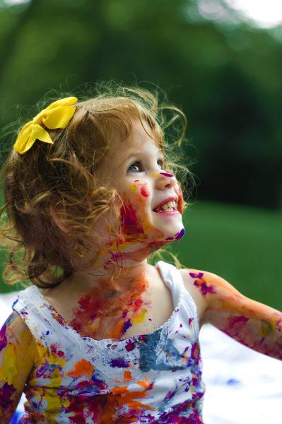enfant souriant couvert de peinture